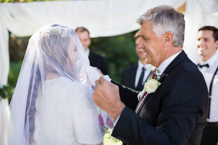 happy father removing veil of his daughter during wedding